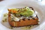 sweet pea + ricotta stuffed squash blossoms, over whipped lardo, grilled toast, + an herb-shallot vinaigrette